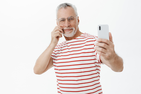 Portrait of enthusiastic charismatic and handsome mature macho bachelor feeling self-assured taking selfie on smartphone to post photo on social web page touching moustache and smiling