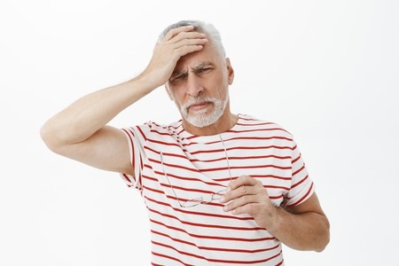 Portrait of senior retired man in striped t-shirt taking off glasses touching forehead and grimacing from pain feeling headache suffering from migraine and painful feelings posing over white wall
