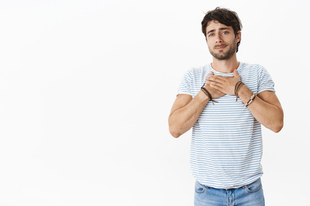 Handsome young masculine guy with blue eyes sincerely sympatizing friend holding hands on breast pursing lips and gazing with empathy and care being touched, feeling heart melting Stock Photo