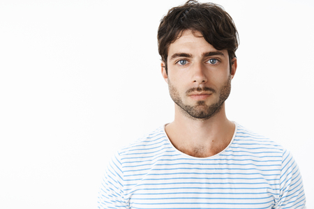 Authentic shot of young attractive guy with slight rash on neck after shaving looking strict and serious at camera with no emotions being chill and confident staring at camera with deep blue eyes