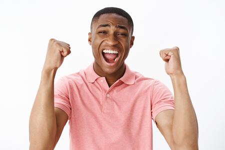 Portrait of happy delighted and amazed attractive african american male fan raising hands with clenched fists in cheer yelling from positive emotions feeling pleased after football team scoring goal