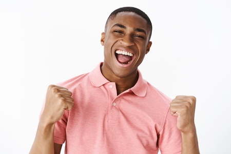 Successful pleased and happy handsome young african american guy in pink shirt clenching fists in victory and cheer yelling yes with happy broad smile being glad to win and receive champion place