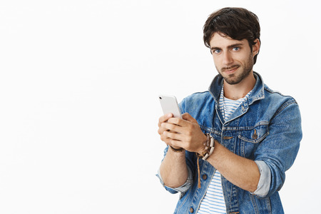 Studio shot of good-looking charming and hot mature man with beard and blue eyes smirking with condifent expression holding smartphone as taking shots on cellphone pleased with good camera