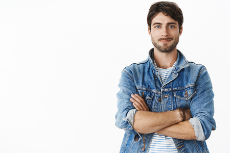 Unaltered shot of charismatic handsome hot adult man with beard and blue eyes in stylish denim jacket over striped t-shirt smiling optimistic, joyful as standing in confident pose with hands crossed Stock Photo