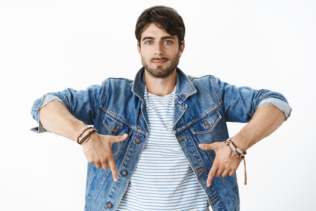 Waist-up shot of chill and joyful young handsome male entrepreneur in denim jacket with blue eyes and bristle smiling confident and assured pointing down posing against gray background