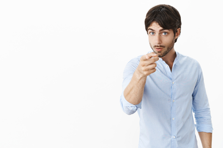 Serious-looking bossy and displeased attractive male entrepreneur in shirt looking, pointing at camera as displeased with unproductive work warning employee he might be fired