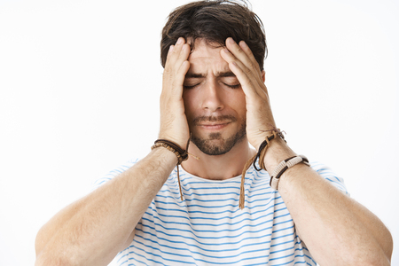 Pressured uneasy male entrepreneur with beard in striped t-shirt having problems at work holding hands on face while eyes closed being tired and concerned, thinking as trying solve troubles Stock Photo