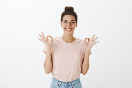 Waist-up shot of carefree and relaxed joyful young female yoga teacher in casual outfit and hairbun showing nirvana orb with both hands and smiling broadly feeling chill and delighted over gray wall