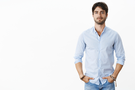 Portrait of handsome successful male entrepreneur in stylish shirt smiling self-assured standing in confident pose with hands in pockets being satisfied with rich life after business got well financed Stock Photo