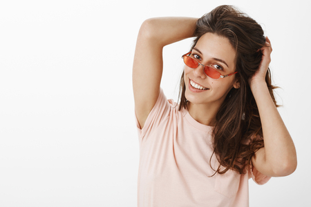Close-up shot of relaxed and joyful attractive stylish modern woman in red sunglasses, tilting head playing with hair as smiling at camera foreplaying and making move as dancing in bar