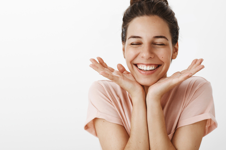 Studio shot of woman feeling happy and joyful cheerfully closing eyes from love and care leaning head on palms smiling broadly feeling with admiration and sympathy standing energized over grey wall