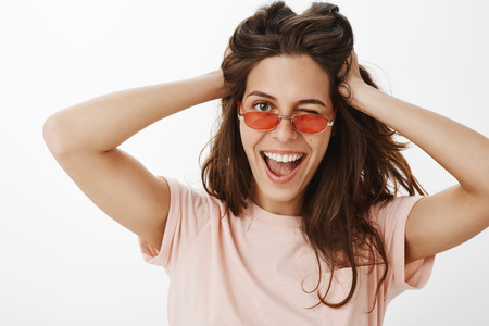 Portrait of charming stylish and confident euroepan  winking joyfully at camera as wearing  trendy sunglasses playing with hair having fun feeling positive