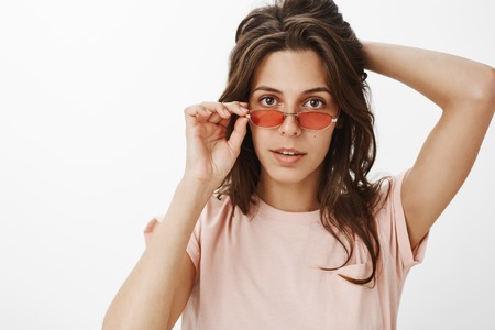 Girl intrigued with interesting offer listening carefully touching rim of red glasses holding hand behind natural beautiful hair standing intrigued and curious against gray background