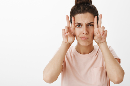 Girl making faces as feeling gloomy trying cheer up fooling around frowning and smirking showing peace gesture sideways standing serious and hilarious over gray background in trendy t-shirt Stock Photo
