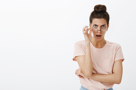 Woman getting shocked and insulted of misbehaviour taking off glasses looking from under forehead with frown dropping jaw from offense and confusion being shook of bad and dumb actions