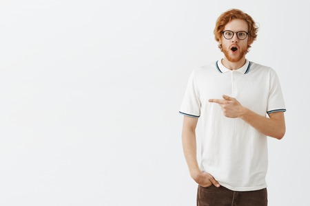 Portrait of amazed and excited handsome redhead young european guy with beard dropping jaw and gasping from surprise and thrill showing amazing thing by pointing left being under impression
