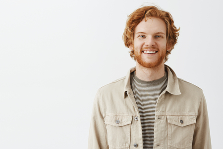 Waist-up shot of good-looking friendly and happy europeanr redhead ordinary guy with beard in casual shirt over t-shirt smiling broadly while standing in queue and talking to manager