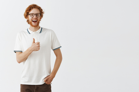 Studio shot of supportive entertained and amused happy redhead bearded guy in casual polo shirt and black glasses smiling broadly showing thumb up liking idea or cheering someone for good effort