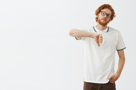 Attractive redhead male snob in glasses and casual outfit tilting head looking left with indifference being unimpressed and careless to situation showing thumbs down expressing dislike and boredom Stok Fotoğraf