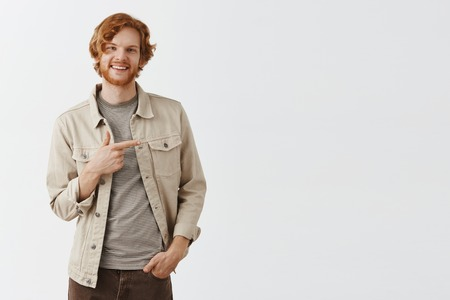 Studio shot of friendly confident and carefree ginger man with sick beard and wavy hair holding hand in pocket while inviting girl for dance pointing right on dance floor and smiling broadly at camera