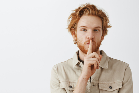 Headshot of mysterious handsome and self-assured redhead mature male with beard and stylish hairstyle saying shh while showing shush gesture with index finge over mouth hiding truth or secret Stock Photo