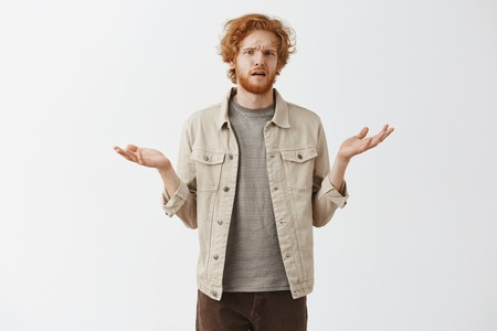 Confused messy and untidy funny redhead young male in jacket over striped t-shirt shrugging with spread palms and clueless expression having no clue where he woke up after drinking all night