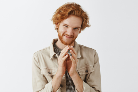 Redhead bearded man has tricky and evil plan on mind steepling fingers over chest and smirking mysteriously squinting at camera standing in beige jacket over gray background. Evil genius in action Stock Photo