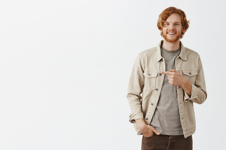 Studio shot of carefree satisfied and confident redhead mature guy with beard in beige outdoor jacket holding hand in pocket pointing left and grinning from joy and good emotions over gray background Stock Photo