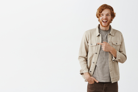 Studio shot fo excited and thrilled enthusiastic redhead guy in jacket over striped t-shirt pointing left and gazing impressed and happy at camera with broad joyful smile over gray background Stock Photo