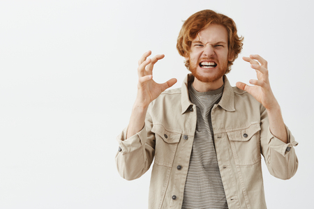 Man explaining how he hates his ex-wife imitating he choking her with bare hands. Portrait of mad and pissed angry redhead guy with beard clenching raised fingers grimacing from anger and outrage