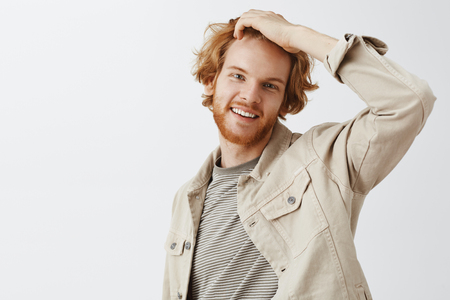 Indor shot of good-looking typical caucasian young man with red color of hair touching head and smiling broadly feeling awkward while reaching cute girl in bar asking phone number over gray background