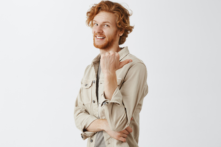 Man suggesting to go and see it. Portrait of pleased happy handsome redhead european man in beige jacket standing half-turned and pointing with thumb right from as if something interesting there