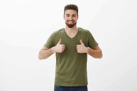 Portrait of cheerful and supportive charming bearded male in t-shirt showing thumbs up and smiling delighted, approving awesome dress on girlfriend Stock Photo
