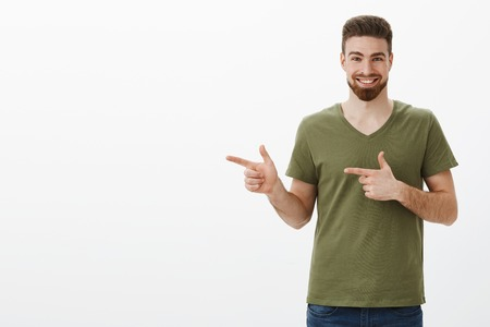 Portrait of enthusiastic and excited attractive bearded guy in olive t-shirt smiling delighted as pointing left with finger pistols to show awesome product over white