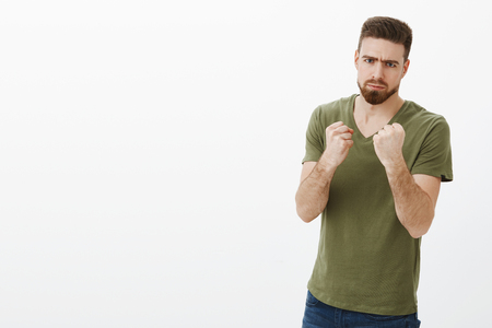 Portrait of handsome serious-looking angry bearded guy in t-shirt frowning making scary face as holding fists like boxer wanting punch and beat