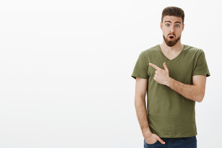Portrait of amazed speechless handsome bearded guy drop jaw from astonishment as seeing incredible product, open mouth and widen eyes from excitement as pointing left Stock Photo
