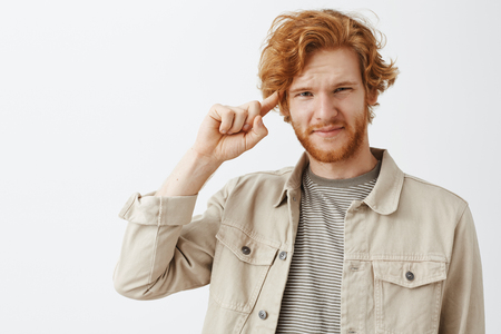 Displeased and dissatisfied handsome ginger guy with beard and wavy red hair rolling index finger over temple in disdain and contempt smirking and squinting at someone acting crazy or stupid Stock Photo