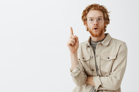 Waist-up shot of creative redhead male genius with wavy hair and beard adding great suggestion standing in eureka pose with raised index finger and folded lips from excitement telling idea Stock Photo