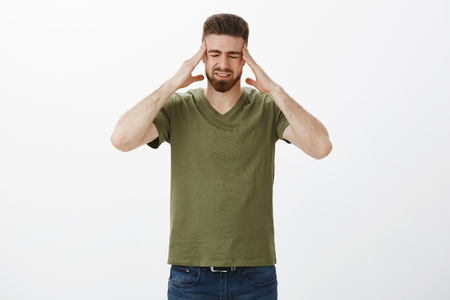 Portrait of uneasy handsome bearded man touching head and temples close eyes from painful feeling of migraine, hate arguing displeased of loud yell as having hangover Stock Photo