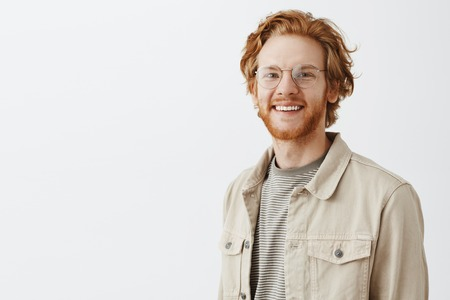 Waist-up shot of pleasant handsome redhead mature guy with beard in transparent glasses and beige jacket over t-shirt smiling friendly and satisfied having great summer walk in evening over gray wall