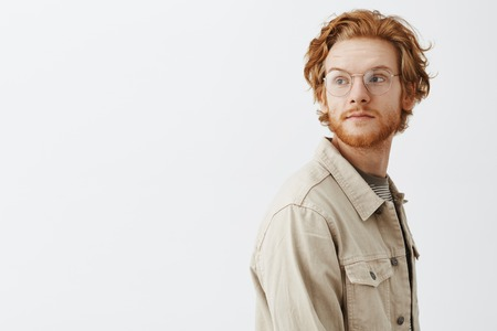 Studio shot of dreamy handsome young redhead guy passing by interesting store and turning left with calm expression being carried away with thoughts wearing beige jacket and transparent glasses