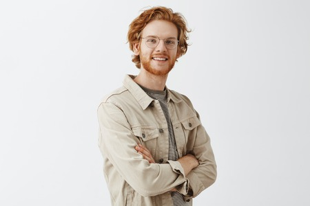 Studio shot fo confident friendly casual male redhead with beard and wavy hairstyle crossing hands on chest and smiling joyfully at camera gazing with satsfied and pleased look over gray wall