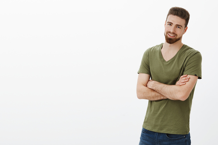 Portrait of handsome enthusiastic bearded guy in confident pose cross hands against body and smirking delighted, assured over white background Stock Photo