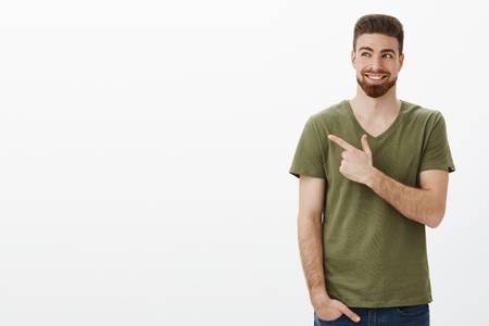 Indoor shot of smart handsome bearded caucasian guy in good mood happy smiling delighted as looking and pointing at upper left corner having great plan pleased against white background