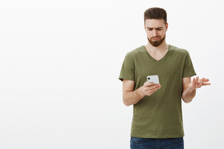 Confused gloomy and troubled attractive boyfriend frowning as looking upset and clueless at smartphone screen shrugging lifting  in dismay, trying understand what written Stock Photo