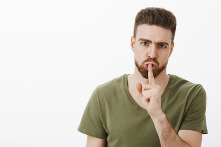 Angry displeased young man with beard frowning and looking irritated as shushing at camera demanding keep silence not talk, holding index finger on mouth while doing shhh over white wall Stock Photo