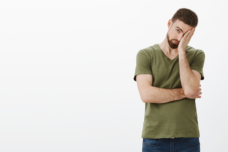 Boyfriend feeling tired wanna break up, standing upset and drained making face palm gesture as exhausted peeking with one eye at camera as fed up of accuses and lies over white background