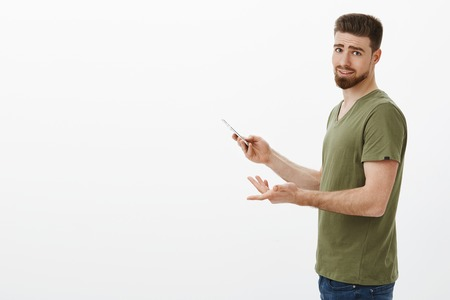 Portrait of irritated cute boyfriend gamer standing in profile with smartphone turning at camera bothered as being distracted from interesting app over white background