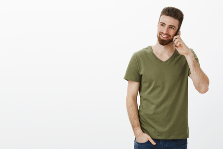 Studio shot of stylish and confident good-looking bearded male entrepreneur talking on smartphone smiling and laughing enjoying conversation looking at upper left corner over white background Stock Photo