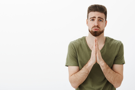 Portrait of cute charming bearded male in need holding hands in pray, supplicating pouting and frowning looking upset as asking favour or help hopefully over white background